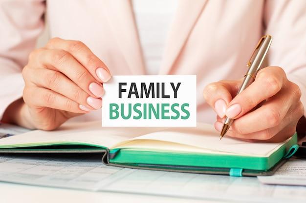 Женщина пишет в блокноте серебряной ручкой и рукой держит карточку с текстом семейного бизнеса. розовый фон, вид спереди. бизнес-концепция.
