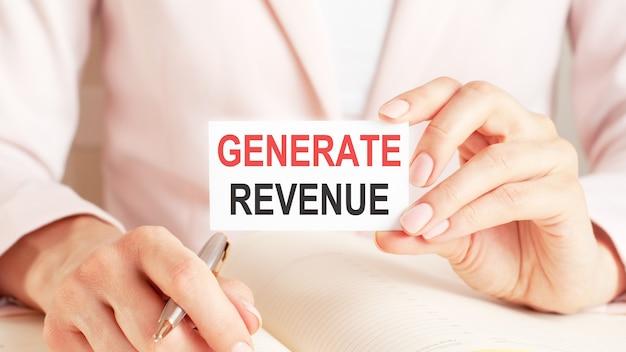 Женщина пишет в блокноте серебряной ручкой и держит в руке карточку с текстом: создать доход.