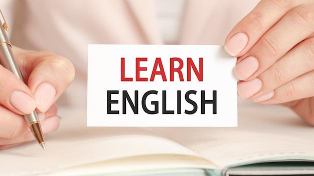 女性は銀のペンとテキスト付きのハンドホールドカードでノートに書き込みます:英語を学びます。ピンクの背景。ビジネスと教育の概念