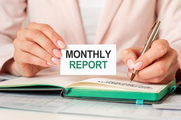 여자는 은색 펜으로 노트북에 씁니다. 텍스트와 함께 손을 잡아 카드 : 월간 보고서. 분홍색 배경, 전면보기. 비즈니스 및 교육 개념.