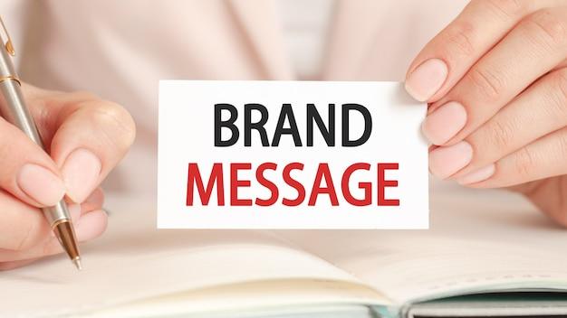Женщина пишет в блокноте серебряной ручкой и рукой держит белую бумажную карточку с текстом: сообщение бренда. концепция бизнеса и финансов.