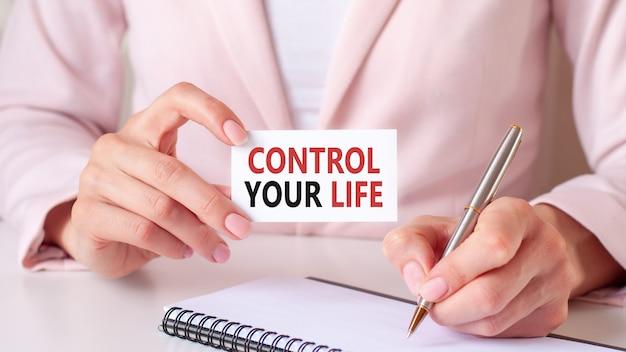 Женщина пишет в блокноте серебряной ручкой и рукой держит карточку с текстом: контролируйте свою жизнь