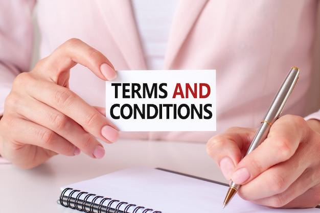 Женщина пишет в блокноте серебряной ручкой и рукой, держащей карточку с текстом: сроки и условия