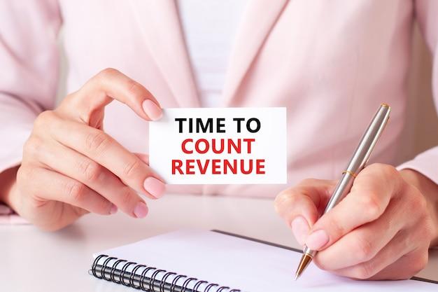Женщина пишет в блокноте серебряной ручкой и рукой, держащей карточку с текстом, время для подсчета доходов. розовый фон, вид спереди. бизнес-концепция.
