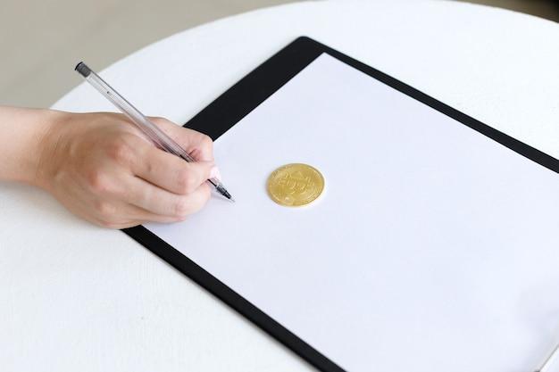 Женщина пишет в планшете с биткойнами на белом фоне