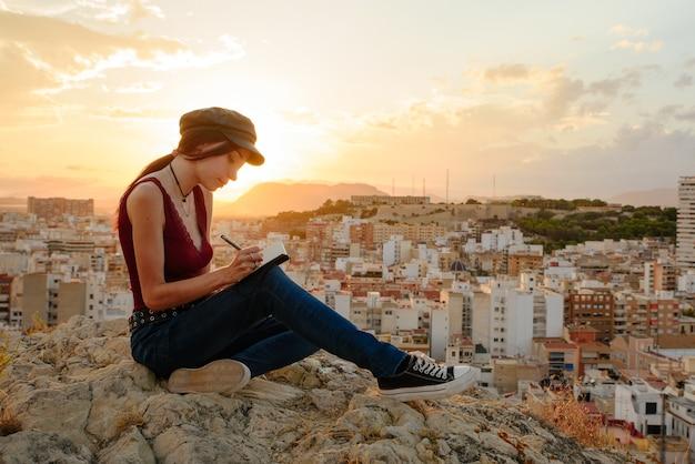 女性は日没時に屋外で彼女のノートブックのフレーズや考えを書きます