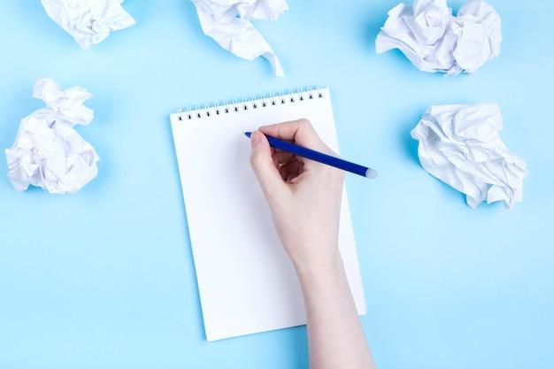 여자는 구겨진 된 종이, 파란색 배경 주위 노트북에서 씁니다. 나쁜 아이디어를 버리고 계획을 세우기 시작하는 개념.