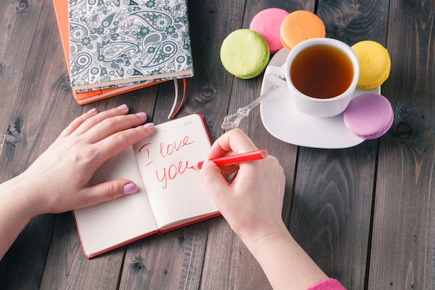 Woman writes letter i love you while drinking coffee