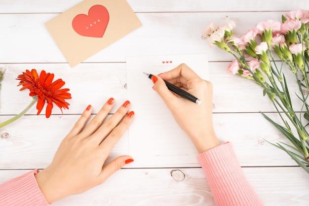 女性は赤いハートの形の数字で白い紙にラブレターを書きます。聖バレンタインデーのお祝いのための手作りのポストカード。2月14日にあなたの恋人や友人に手紙を送ってください。