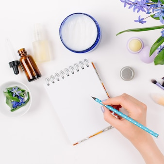 A woman writes in a notebook  blue spring bouquet homemade cosmetics and accessories