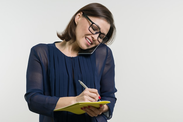 Woman writes on notebook and calling phone