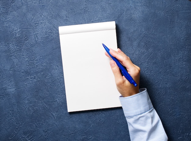 Woman writes in notebook on dark blue table, hand in shirt holding a pencil, sketchbook drawing,