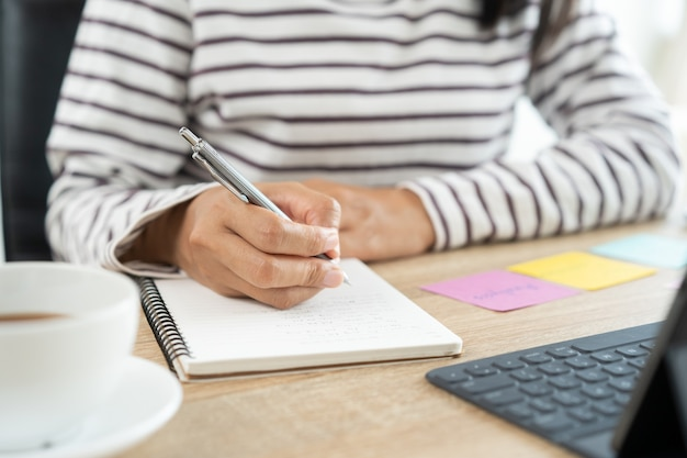 Woman writes in notebook with a pencil at the table
