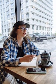 여자는 카페나 레스토랑에 앉아 노트북에 메모를 씁니다.