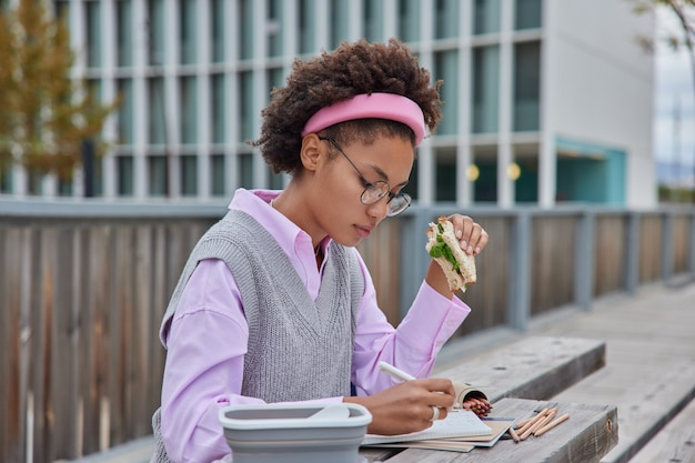 Woman writes notes in notebook puts down educational ideas for university course work prepares informative research does homework eats tasty sandwich poses outdoors against cityscrapers