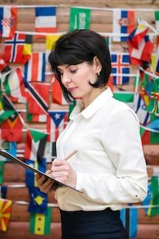 여자는 세계의 국기로 만들어진 벽의 배경에 대해 종이에 씁니다.