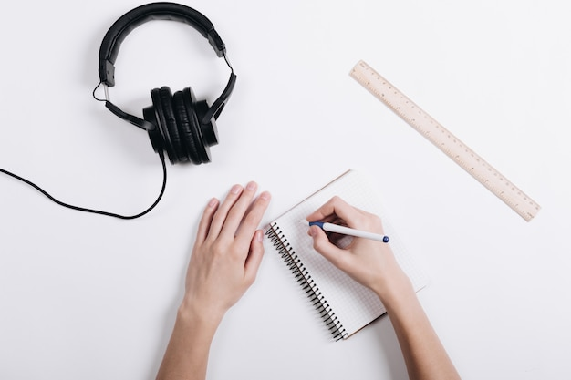 Woman writes a pen in a notebook on a white table, next lie headphones and measuring ruler
