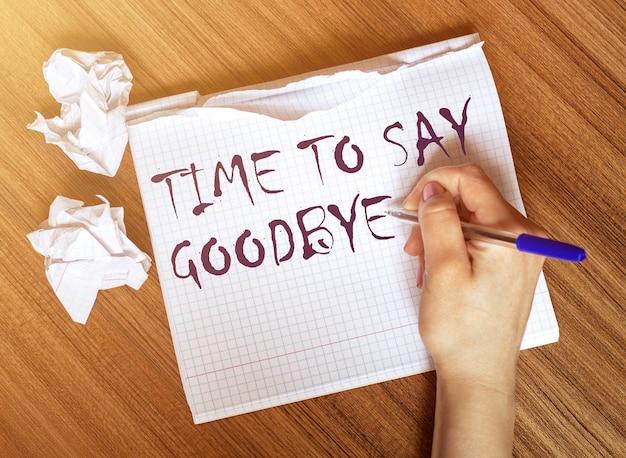女性がテキストを書くノートに別れを告げる時間