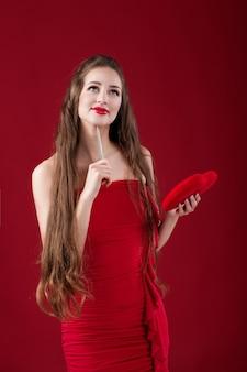 Женщина пишет ручкой на красном сердечке на день святого валентина