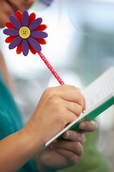 Woman writing on the agenda with a fun pen
