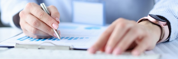 Woman writing ballpoint pen in documents with graphs closeup.