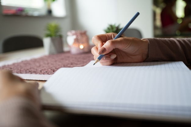 Woman writing in blank notebook on wooden desk