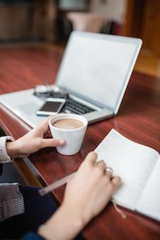 Woman writing in book while having tea