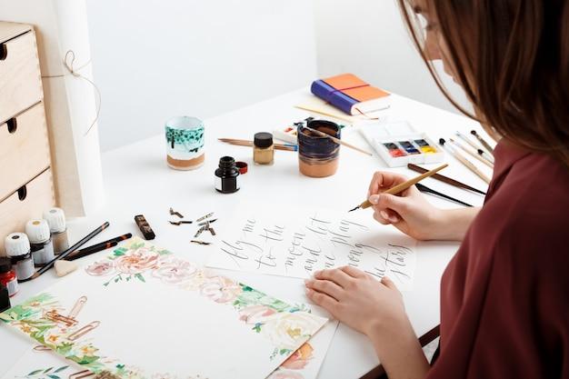 Woman writing calligraphy on postcards
