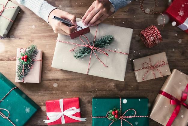 Woman writing christmas greeting card on gift box