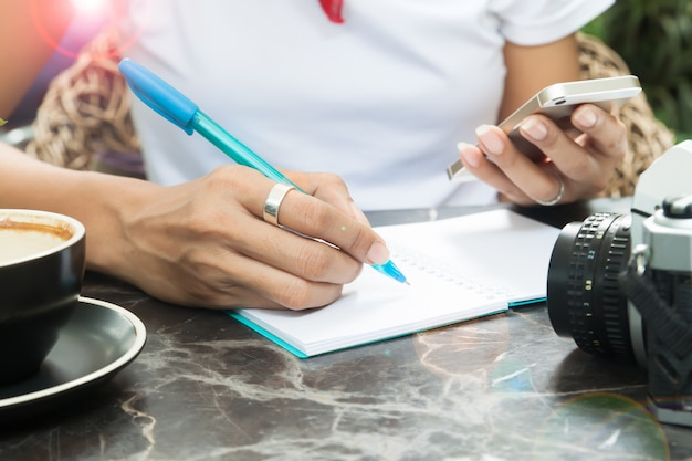 Woman writing on diary and using smartphone