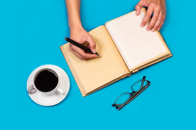 Woman writing in a diary with a cup of coffee on a blue background in a top view