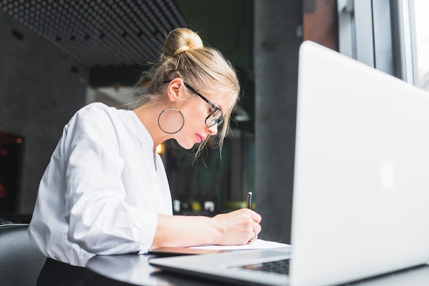 Woman writing on document with laptop on desk