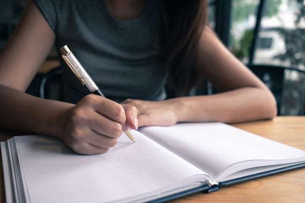Женщина записывает свою идею на ноутбуке в кафе