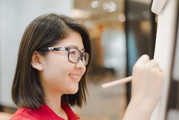 Woman writing on flip chart paper