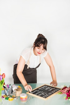 Woman writing flowers in stock on slate with chalk over desk