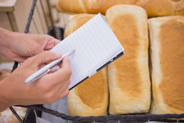 A woman writing a grocery list above bread loaf