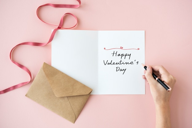 Woman writing a happy valentine's day card