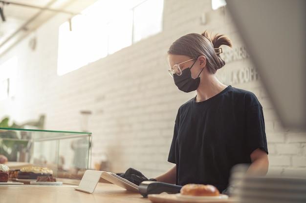 고객의 전자 태블릿 순서로 작성하는 여성
