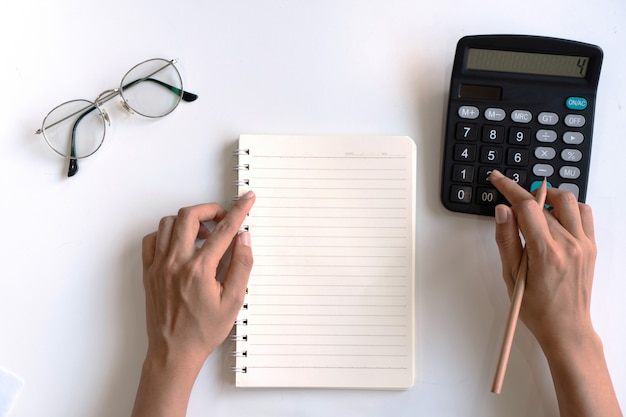 Woman writing on notebook while using calculator on desk