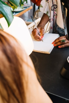 Woman writing on notebook with pen at counter
