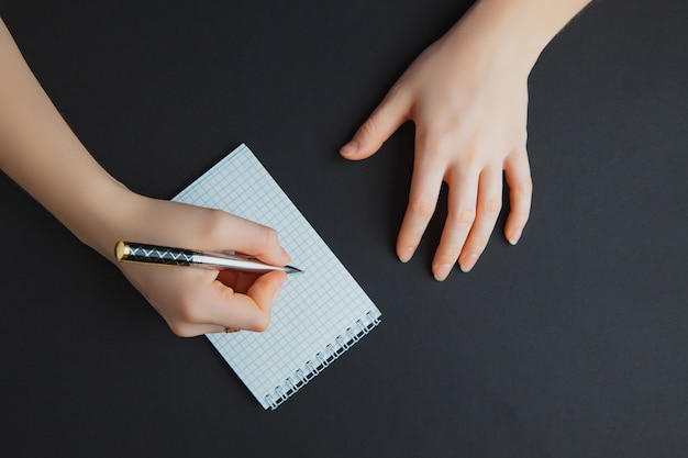 Woman writing in notepad at black table