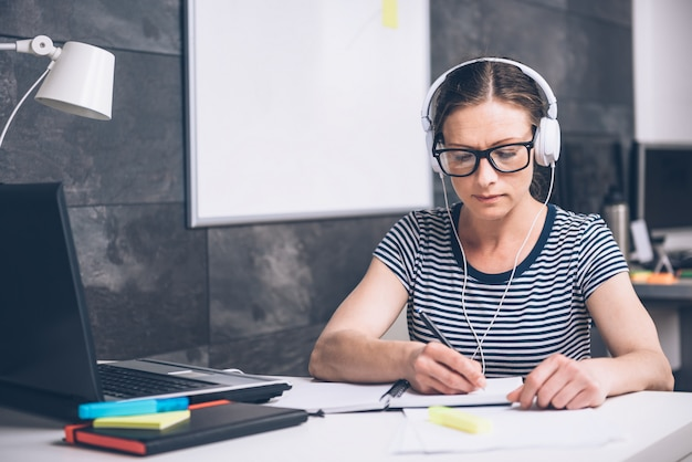 ノートを書くと、オフィスで音楽を聴く女性