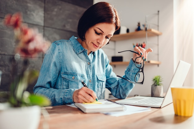 Woman writing notes in note pad and holding eyeglasses