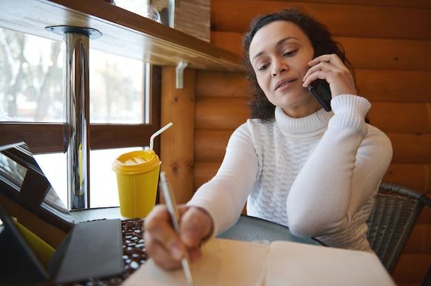 Женщина пишет в дневнике во время переговоров, сидя у окна в деревянном кафе. бизнес-концепция онлайн