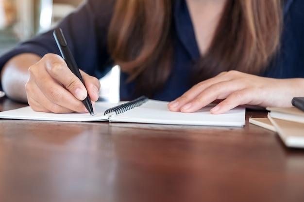 Женщина, пишущая на пустой записной книжке на столе в кафе