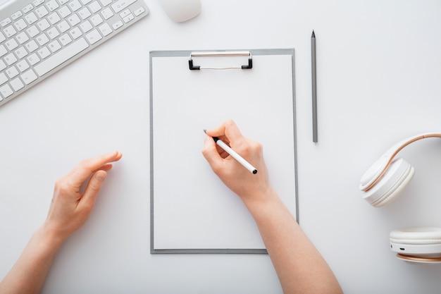 リストを行うためにメモ帳の空のリストに書いている女性。女性の手は、オフィスの職場で紙のタブレットにスケッチをします。女性の手は白いテーブルの上のワークデスクでノートに書き込みます。上面図。
