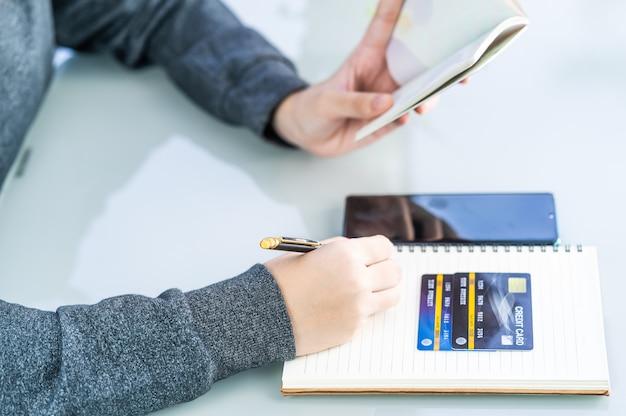 クレジットカードとスマートフォンのデスクとノートに書く婦人