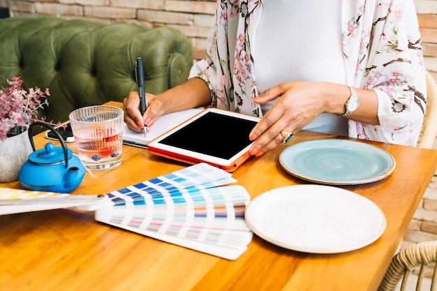 디지털 태블릿 노트북에 쓰는 여자; 나무 테이블에 접시와 색상 견본