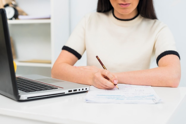 Woman writing on papers at table with laptop