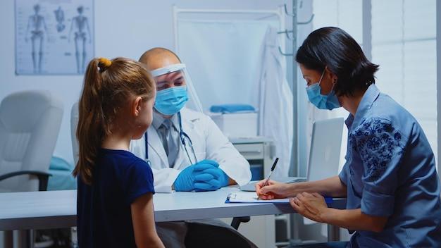 医師の指示を聞いてクリップボードに処方箋を書く女性。 covid-19の間に医療サービス、相談、病院での治療を提供するマスクを備えた医学の小児科医の専門家